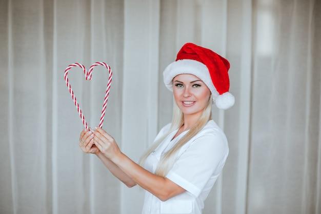Giovane medico in camice medico bianco e cappuccio rosso di babbo natale in posa con le caramelle su sfondo bianco.