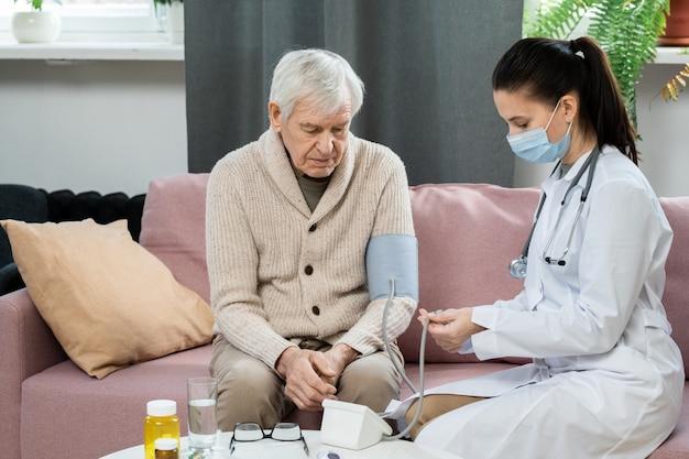 Giovane medico in camice bianco e maschera protettiva che usa il tonometro mentre è seduto sul divano accanto a un uomo anziano malato e misura la sua pressione sanguigna