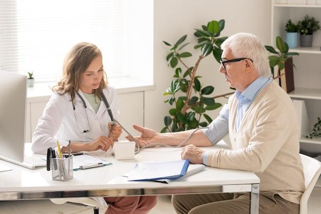Giovane medico in whitecoat utilizzando il tonometro durante la misurazione della pressione sanguigna di un uomo anziano durante la consultazione medica