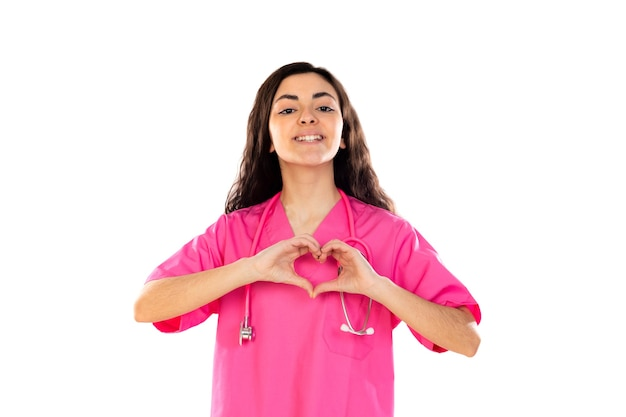 Giovane medico con l'uniforme rosa isolato su un muro bianco