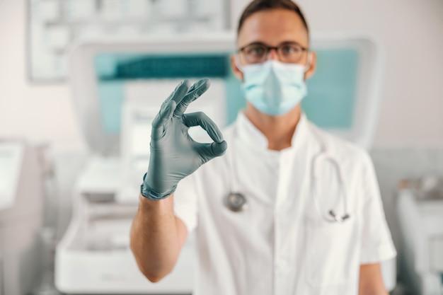 Giovane medico con guanti di gomma e maschera facciale in piedi in ospedale e mostrando bene.