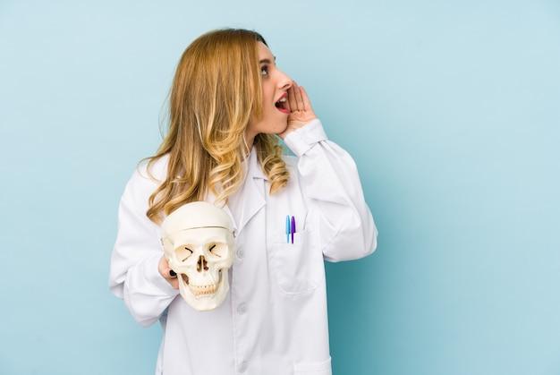 La giovane donna di medico che tiene un cranio ha isolato gridando e tenendo il palmo vicino alla bocca aperta. Foto Premium