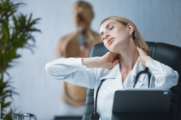 Un giovane medico lavora seduto a un tavolo nel suo ufficio. il dottore si sente stanco, si tiene il collo