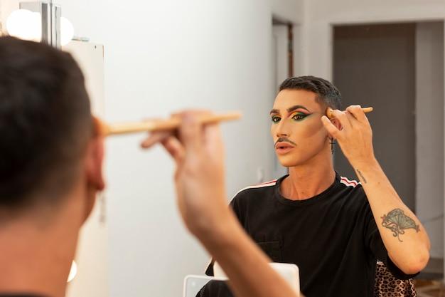 Giovane artista drag queen che si trucca nel camerino