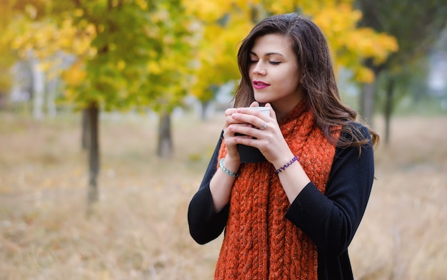 Giovane ragazza che sogna con una tazza di caffè (tè) per una passeggiata nel parco all'aperto. tempo autunnale.