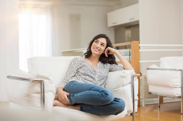 Giovane donna di sogno che si siede sul divano di casa