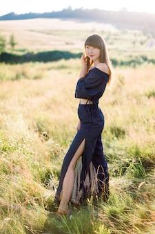Giovane donna caucasica sognante in vestiti eleganti neri che cammina sul prato estivo al giorno pieno di sole, distogliendo lo sguardo