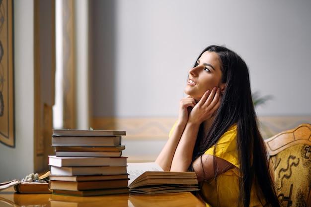 Libri di lettura della ragazza studentessa giovane sognatore ed entusiasta presso la vecchia biblioteca