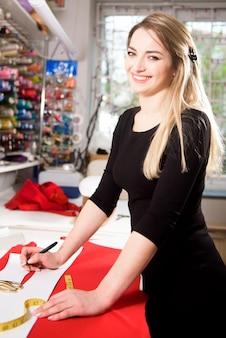 La giovane donna del sarto da donna cuce i vestiti sulla macchina da cucire.