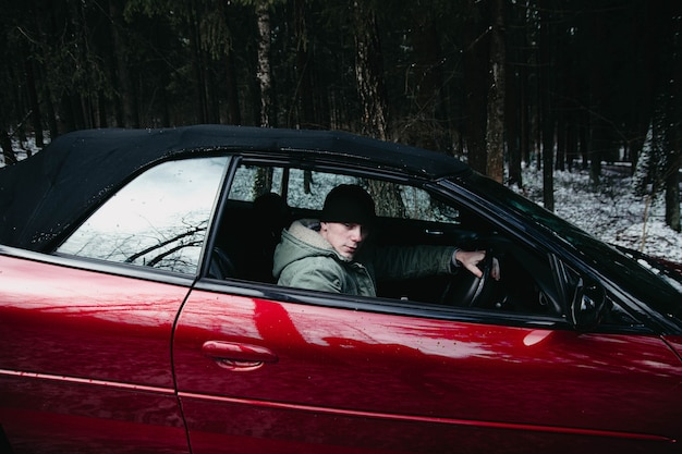 Giovane conducente in un'auto decappottabile rossa nella foresta invernale concetto di auto costosa