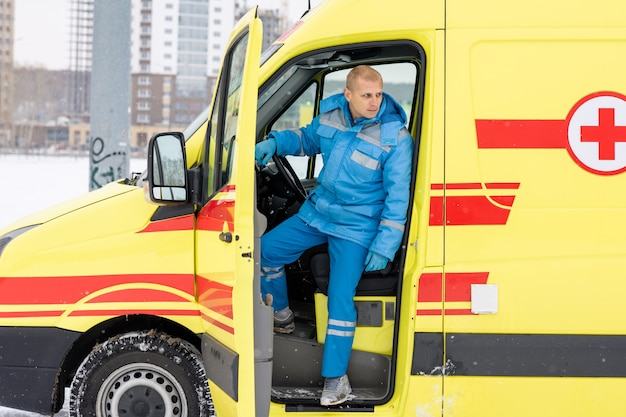 Giovane conducente seduto a guidare in ambulanza in attesa che un gruppo di paramedici torni con la persona malata