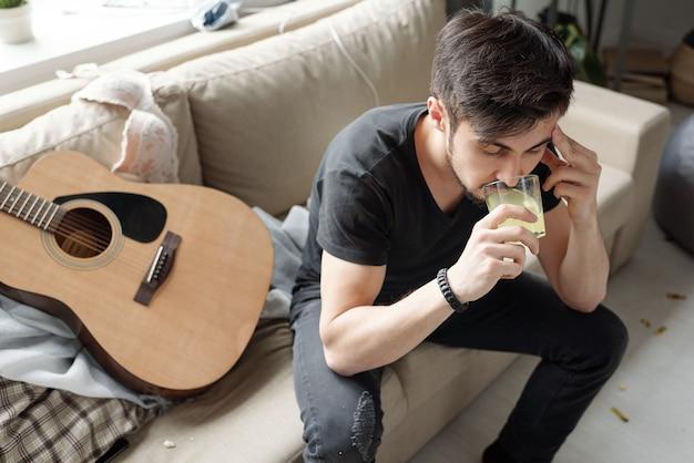 Giovane uomo ubriaco con mal di testa che si siede sul divano con la chitarra e bere pillola sciolta in un bicchiere d'acqua dopo la festa