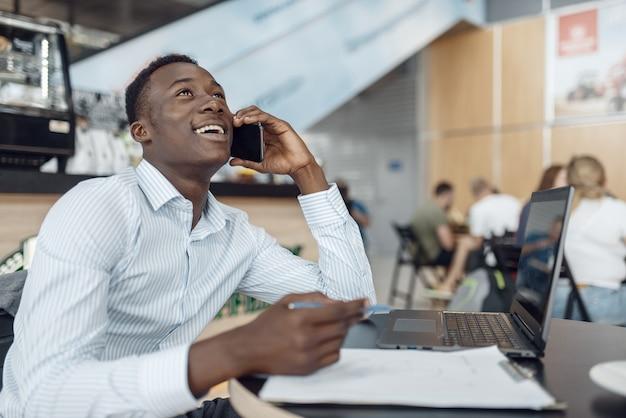 Giovane uomo d'affari ebano che parla dal telefono nella caffetteria dell'ufficio. l'uomo d'affari di successo beve caffè nella food-court, uomo di colore in abbigliamento formale
