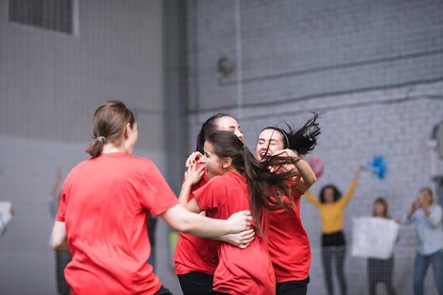 Giovani sportive estatiche in magliette rosse che si abbracciano dopo il gol di successo durante la partita di calcio