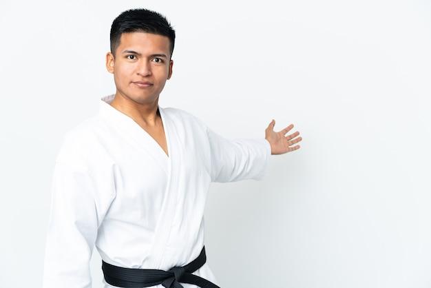 Giovane uomo ecuadoriano che fa karate isolato su sfondo bianco allungando le mani di lato per invitare a venire