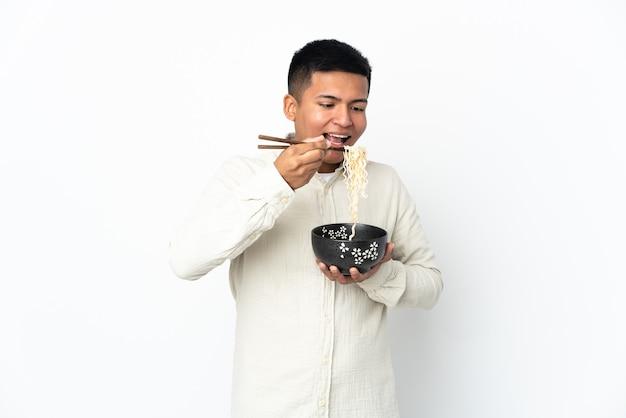 Giovane uomo ecuadoriano isolato su sfondo bianco in possesso di una ciotola di spaghetti con le bacchette e mangiarlo