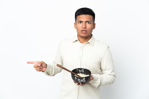 Giovane uomo ecuadoriano isolato su sfondo bianco sorpreso e rivolto verso il lato mentre si tiene una ciotola di spaghetti con le bacchette