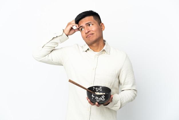 Giovane uomo ecuadoriano isolato sul muro bianco con dubbi e con confondere l'espressione del viso mentre si tiene una ciotola di spaghetti con le bacchette