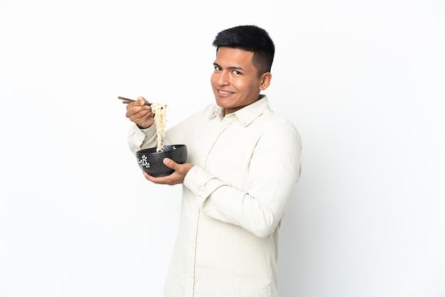 Giovane uomo ecuadoriano isolato sul muro bianco che tiene una ciotola di spaghetti con le bacchette
