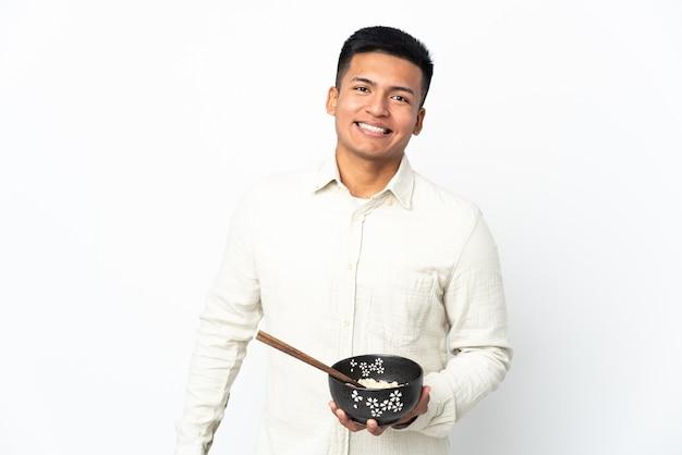 Giovane uomo ecuadoriano isolato sul muro bianco sorridente molto mentre si tiene una ciotola di spaghetti con le bacchette