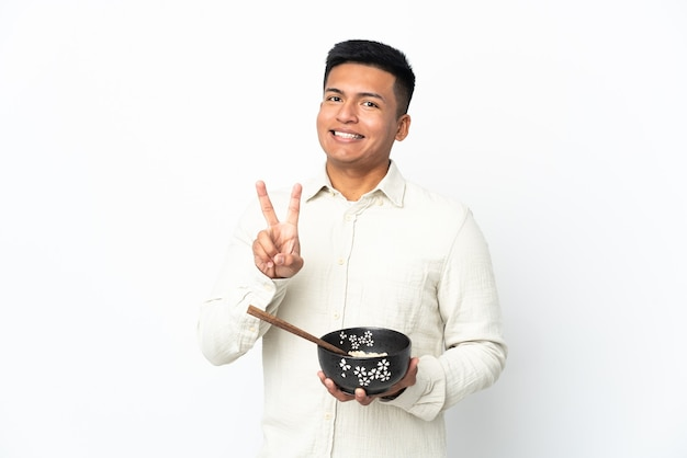 Giovane uomo ecuadoriano isolato sul muro bianco sorridendo e mostrando il segno di vittoria mentre si tiene una ciotola di spaghetti con le bacchette