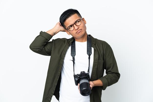 Giovane fotografo ecuadoriano isolato su sfondo bianco avendo dubbi