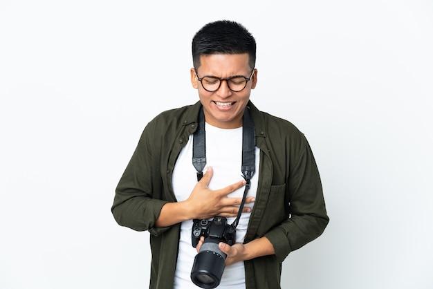 Giovane fotografo ecuadoriano isolato su sfondo bianco che sorride molto