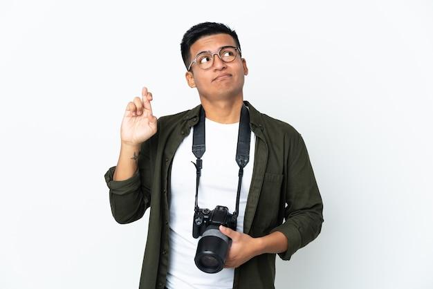Giovane fotografo ecuadoriano isolato su sfondo bianco con le dita incrociate e augurando il meglio