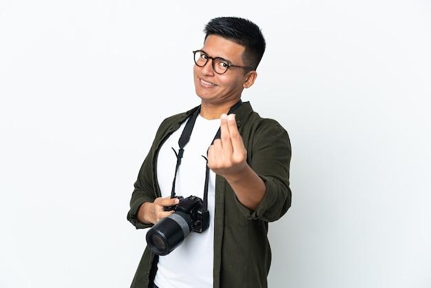 Giovane fotografo ecuadoriano isolato sul muro bianco che fa gesto di denaro