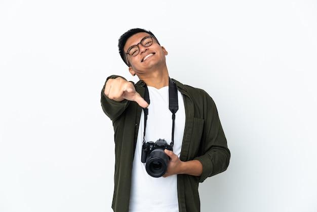 Giovane fotografo ecuadoriano isolato sul muro bianco che punta davanti con felice espressione