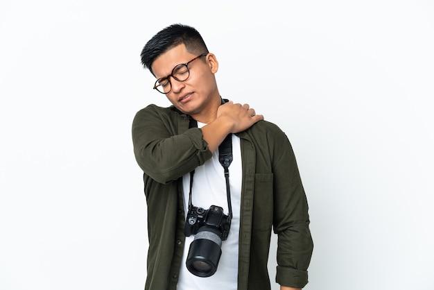 Giovane fotografo ecuadoriano isolato sul muro bianco che soffre di dolore alla spalla per aver fatto uno sforzo