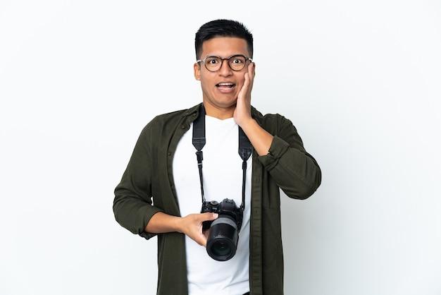 Giovane fotografo ecuadoriano isolato sul muro bianco con espressione facciale sorpresa e scioccata