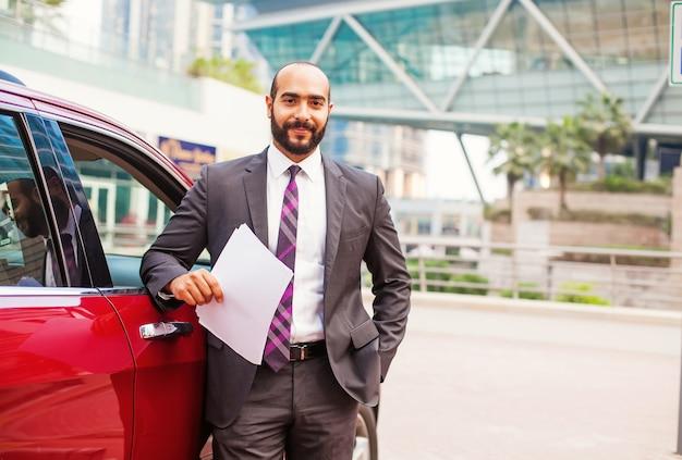 Giovane uomo d'affari egiziano in piedi vicino alla macchina e con in mano dei documenti