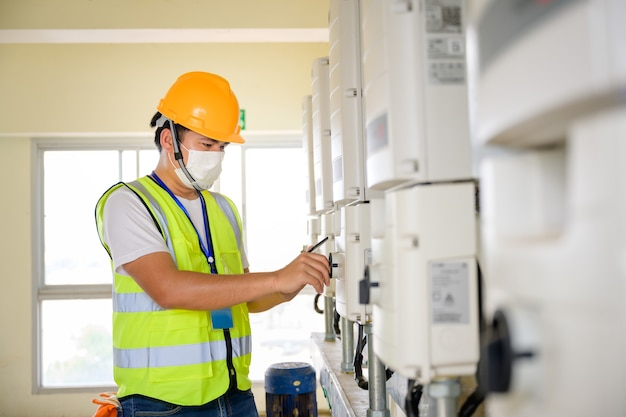 Giovane ingegnere elettrico che indossa una maschera ispezionare il pannello di controllo fotovoltaico e il sistema di controllo elettrico interno da un tecnico dell'impianto fotovoltaico.