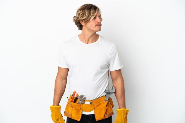 Giovane uomo biondo elettricista isolato su sfondo bianco che guarda al lato