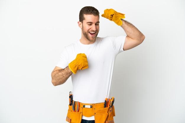 Uomo del giovane elettricista sopra la parete bianca isolata che celebra una vittoria