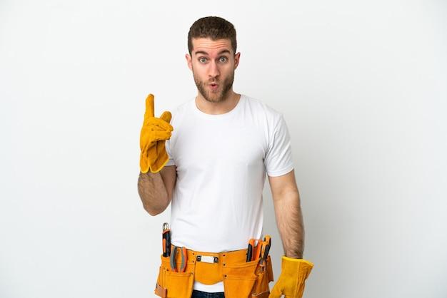 Il giovane elettricista sopra il muro bianco isolato con l'intenzione di realizzare la soluzione sollevando un dito