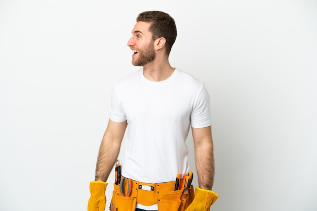 Uomo giovane elettricista sopra la parete bianca isolata che ride in posizione laterale
