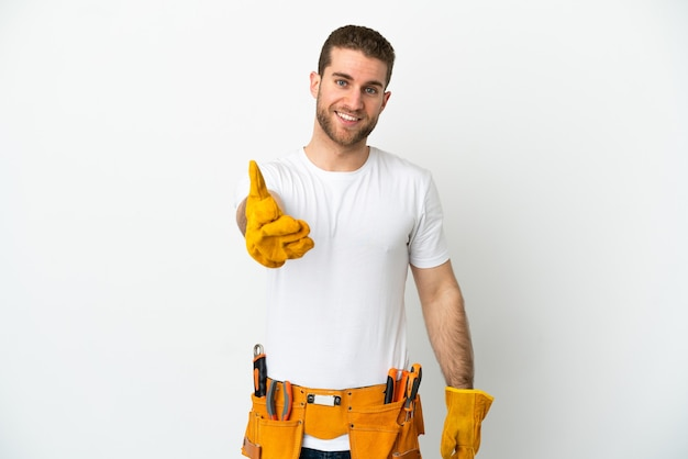 Giovane elettricista sopra il muro bianco isolato che stringe la mano per aver chiuso un buon affare