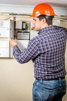 Giovane elettricista che ripara quadro elettrico a casa
