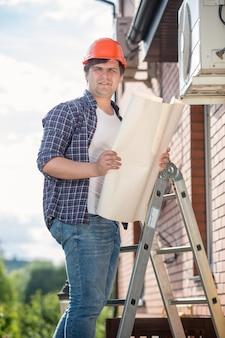 Giovane elettricista in piedi su una scala alta e tenendo il piano della casa plan