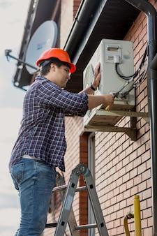 Giovane elettricista in piedi su una scala a pioli e che ripara il sistema di aria condizionata