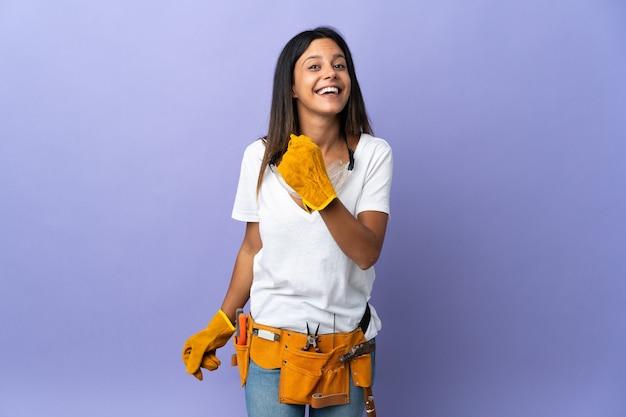 Giovane donna elettricista isolata su sfondo viola che celebra una vittoria
