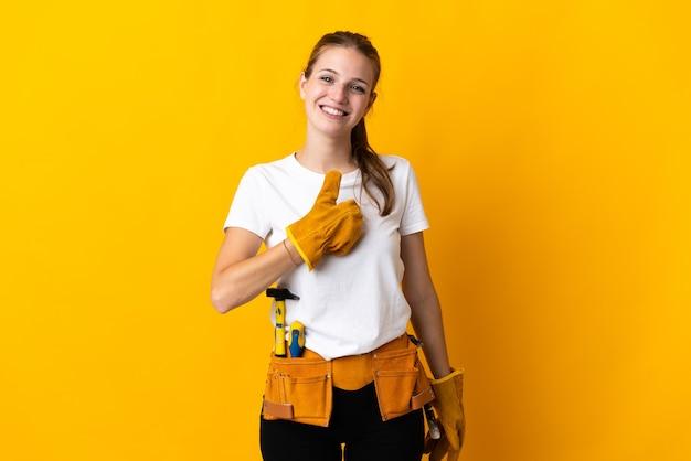 La giovane donna dell'elettricista isolata sulla parete gialla che dà i pollici aumenta il gesto