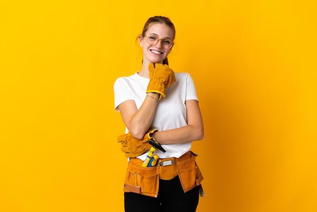 Donna giovane elettricista isolata sul giallo con gli occhiali e sorridente
