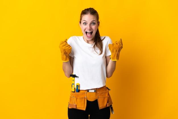 Giovane donna elettricista su giallo che celebra una vittoria nella posizione del vincitore