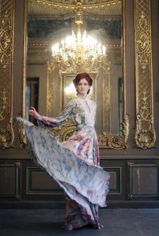 Giovane donna di eleganza con vestito volante nella stanza del palazzo