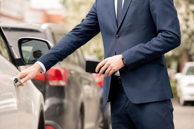 Giovane uomo d'affari elegante in abiti da cerimonia aprendo la portiera dell'auto o del taxi mentre si va per un incontro con i partner