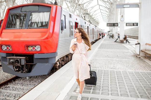 Giovane ed elegante donna d'affari che cammina con valigia e tazza di caffè sulla piattaforma della stazione ferroviaria