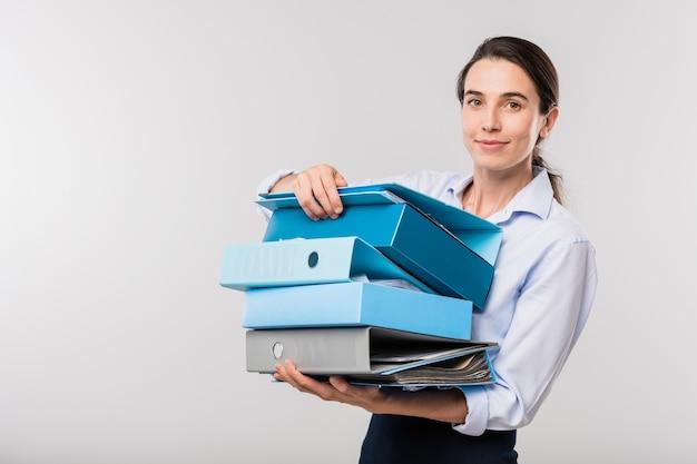 Giovane imprenditrice elegante con una pila di cartelle con documenti finanziari in piedi davanti alla telecamera